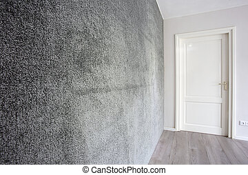Grey fabric carpet of fur on the wall modern interior, white door and wall in a clean house