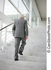 Grey-haired businessman climbing steps