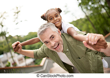 Grey-haired daddy having fun with his cute lovely daughter