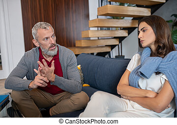 Grey-haired man moralizing his young and beautifuls pouse