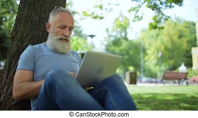 Grey haired man sitting under tree and typing