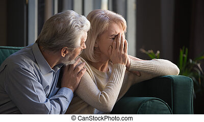 Grey haired man supporting crying unhappy mature woman