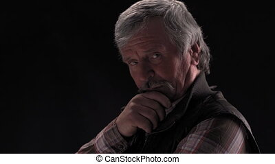 Grey haired senior man looking down then on at camera and smile with camera slide in wearing jacket in semi lit light studio isolated on black background. Prores 422.