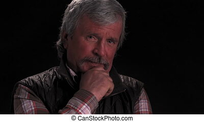 Grey haired senior man nodding head in agreement looking at then on at camera and smile with camera slide out wearing jacket in semi lit light studio isolated on black background. Prores 422.