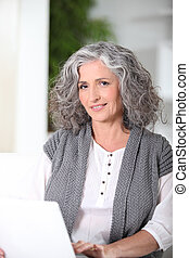 Grey-haired woman sat using laptop at home