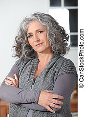Grey haired woman stood in the kitchen with her arms folded