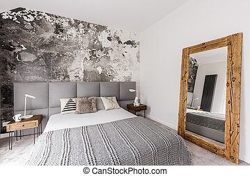 Grey, king-size bed in bedroom - Grey king-size bed in a...