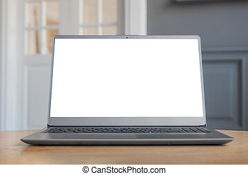 Grey laptop with white blank screen on wooden table in home interior
