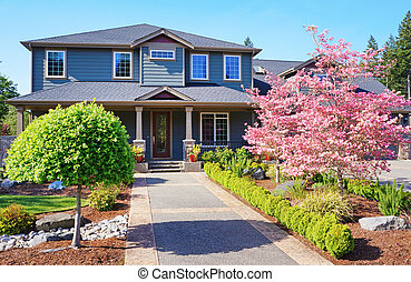 Grey lareg luxury house with spring blooming trees.