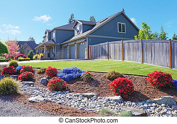 Grey large luxury house with spring blooming red and blue flowers.