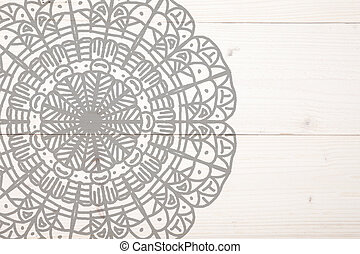Grey mandala on white wooden background