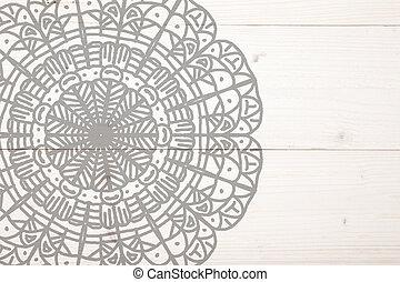Grey mandala on white wooden background