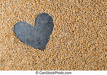 Grey metal heart from seeds of ripe golden wheat