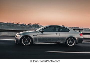 Grey metallic sedan luxury car with ,side view on the road.