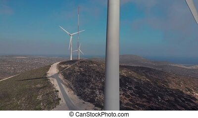 grey modern windmill with large rotating blades close aerial...