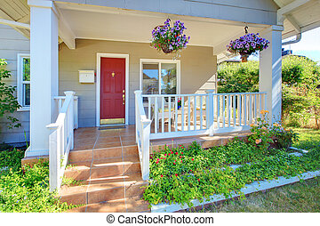 Grey house porch with red door and white railings.