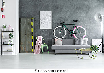 Grey open space interior - Black bike above grey sofa chair...