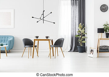 Grey open space interior - Lamp above wooden table and grey...