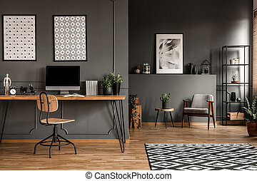 Grey open space interior - Posters on grey wall above wooden...