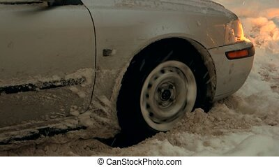 Grey passenger car stuck in snow. Close up wheel of car...