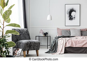Grey patterned armchair in bedroom