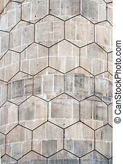 grey polygon hexagonal pattern on an old curved concrete block exterior wall