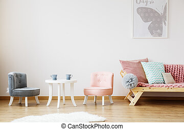 Grey poster above sofa with mint patterned pillow and pink...