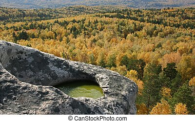 Grey rock with small green lake over autumn wood
