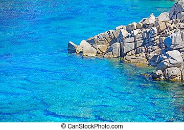 grey rocks on the blue water in Capo Testa