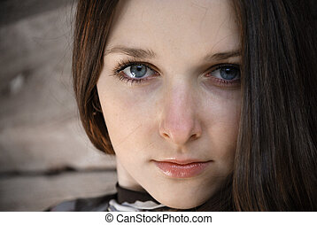 Grey scrutiny of teenage girl with long brown hair, close-up