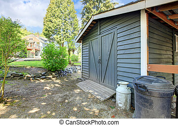 Grey shed with house on the back.