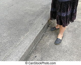grey shoes on asian female legs standing on the floor