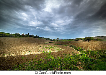 Grey sky over a brown field in Tuscany