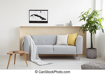 Grey sofa between wooden table and plant in modern living room interior with poster. Real photo