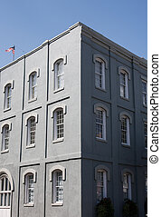 Grey Stucco Building with White Windows - An old grey stucco...