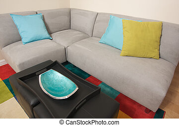 Grey Suede Couch Corner Area with colorful rug and pillows.