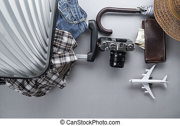 Grey suitcase packed for travelling with min airplane, clothes and accesories on grey background - travel concept - Image