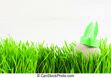 Grey textile egg with paper ears rabbit decoration in grass with copy space