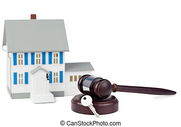 Grey toy house model with a key and a brown gavel against a...