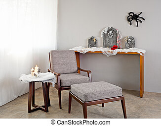 Grey upholstered chair in Halloween seting