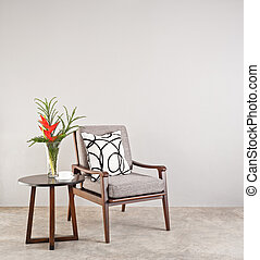 Grey upholstered chair in living room with flowers