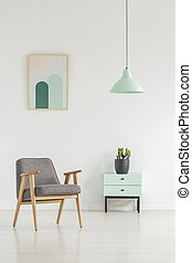 Grey wooden armchair next to cabinet with plant in white apartment interior with poster. Real photo