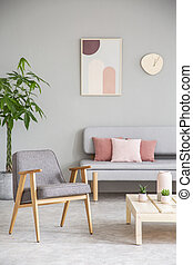 Grey wooden armchair next to table in living room interior with poster above couch. Real photo