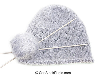 Grey woolen knitted mohair cap with clew and knitting needles