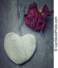 Grey zen heart shaped rock with a half dead rose on a tile...