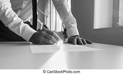 Greycale image of a man signing contract or document