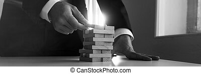 Greycale panorama view of businessman placing wooden domino in a tower