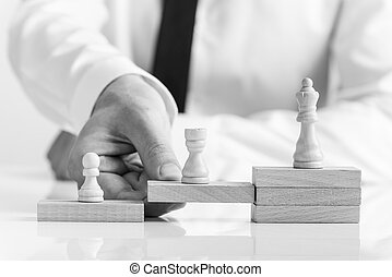 Greyscale image of businessman supporting chess pieces