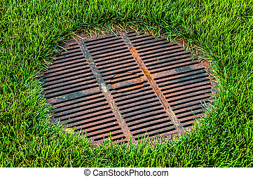 Gridded sewer manhole on green lawn