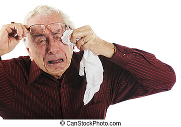 A senior man wiping his eyes as he cries openly. Isolated on white.